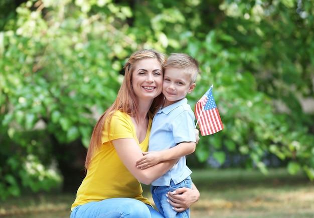 Madre e hijo con bandera americana en el parque