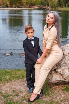 Madre e hijo caminan en el parque por el lago