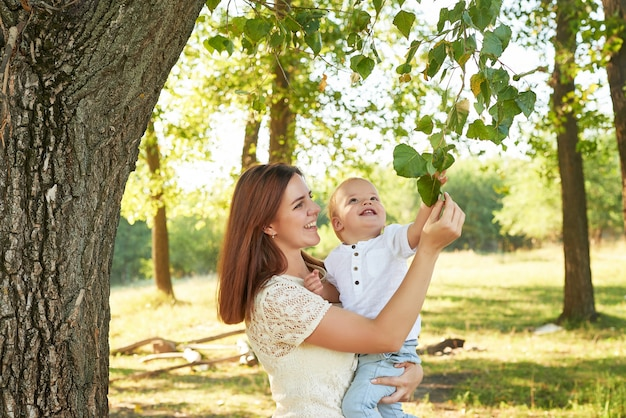 Madre e hijo caminan por el parque en verano al atardecer
