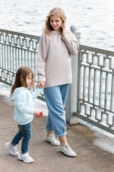 Madre e hijo caminando por la orilla del mar