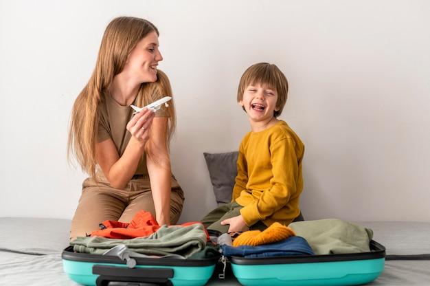Madre e hijo en casa con figurilla de avión y equipaje