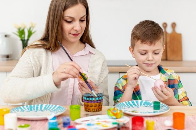 Madre e hijo en casa pintando huevos