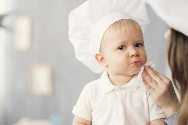 Madre e hijo en la cocina, sombreros blancos de chef, mamá limpia al bebé con ayuda de una servilleta
