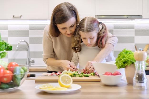 Madre e hijo cocinando juntos en casa en la cocina