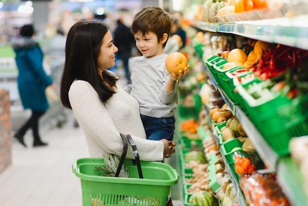 Madre e hijo comprando frutas en un mercado de agricultores