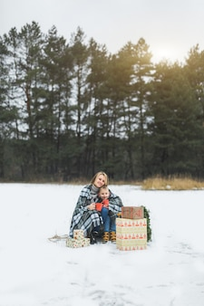 Madre e hijo cubiertos con cuadros escoceses, sosteniendo tazas con bebidas calientes, sentado en un trineo decorado de madera
