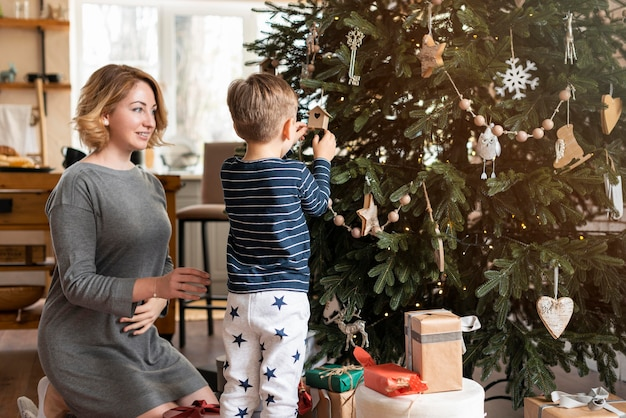 Madre e hijo decorando el árbol juntos