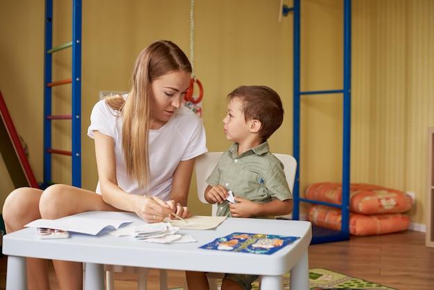 Madre e hijo dibujan en una mesa dentro de la habitación.