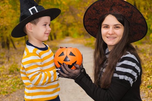 Madre e hijo en disfraces de halloween juegan en el bosque de otoño.