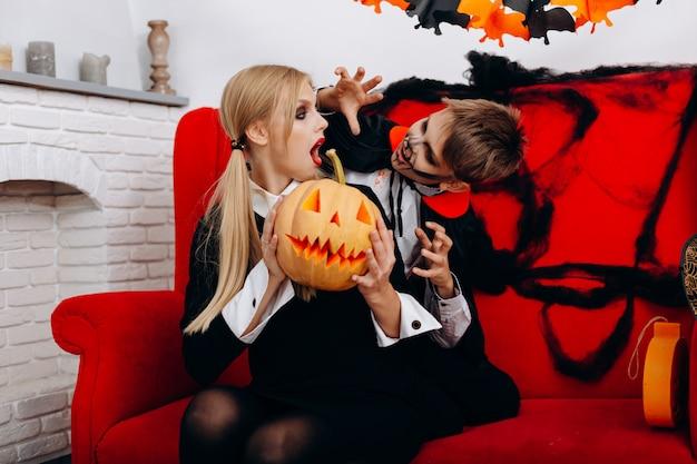 Madre e hijo se divierten en el sofá rojo. chico mujer de miedo. festividad de todos los santos