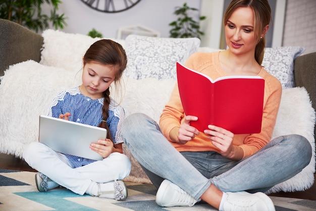 Madre e hijo enfocados estudiando con tecnología.