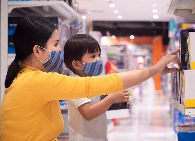 Madre e hijo están comprando en una juguetería y usan una máscara protectora en la cara del brote de aire infectado con virus.