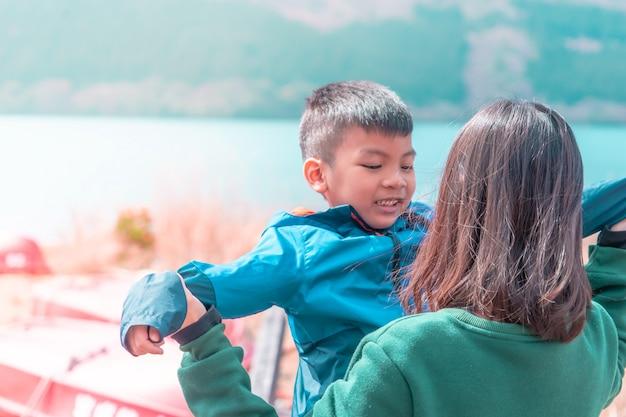 Madre e hijo están jugando cerca del lago ashi en hakone, japón