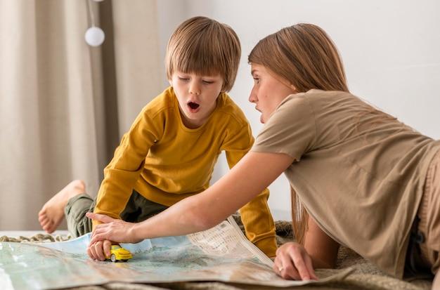 Madre e hijo jugando con estatuilla de coche y mapa.