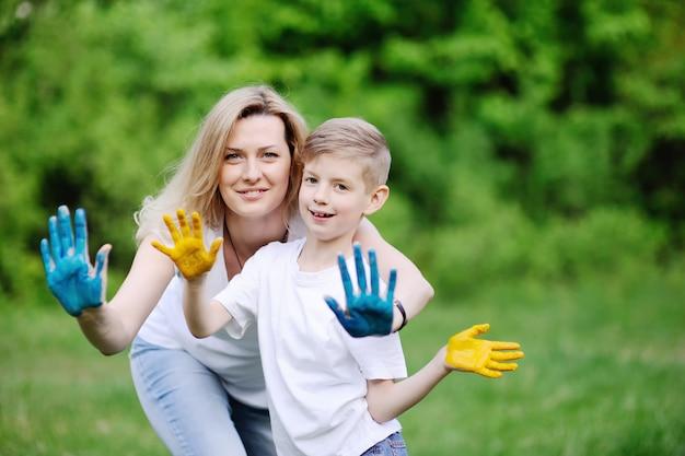 Madre e hijo jugando en el fondo de árboles verdes. manos de mamá e hijo untadas con pintura coloreada.