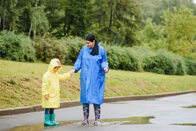 Madre e hijo jugando bajo la lluvia, con botas e impermeables