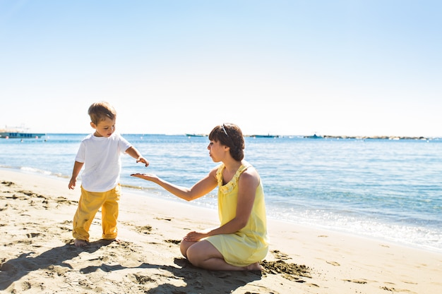 Madre e hijo jugando en la playa tropical de verano