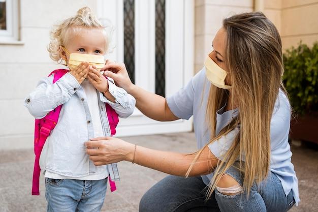 Madre e hijo con máscaras médicas.