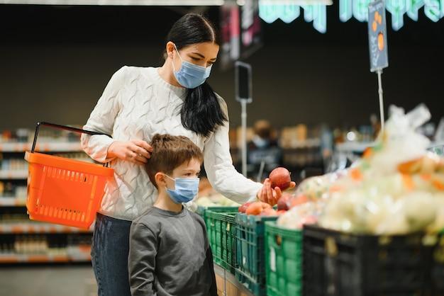 Madre e hijo en mascarilla en el centro comercial