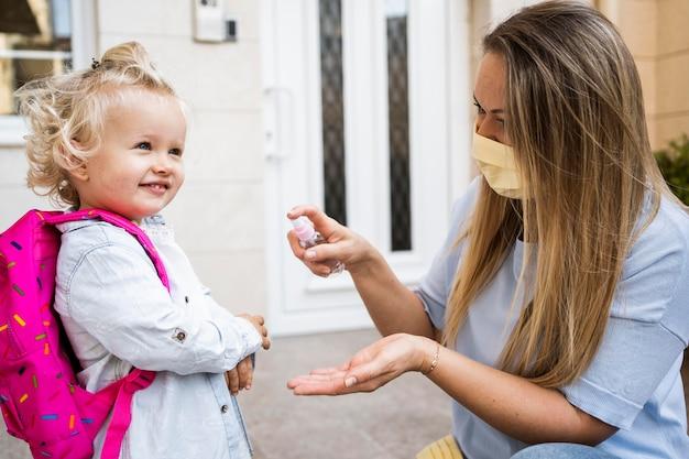 Madre e hijo con mascarillas médicas y desinfectante de manos