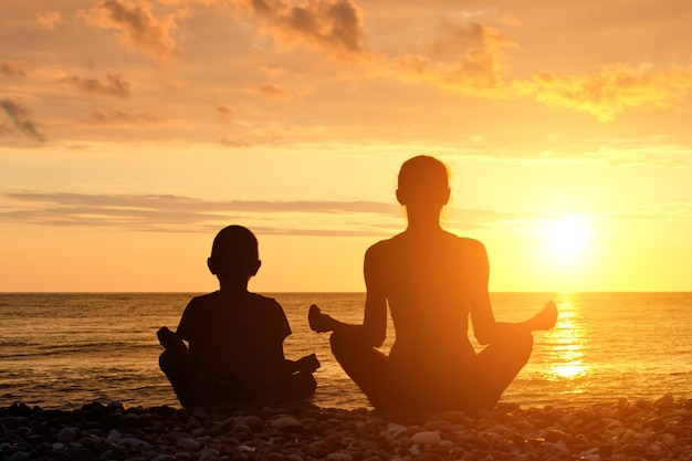 Madre e hijo meditan en la playa en posición de loto