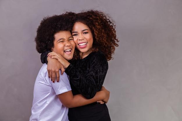 Madre e hijo negros abrazándose sobre fondo gris