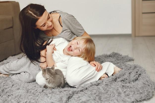 Madre e hijo pequeño divertido en casa con un gato