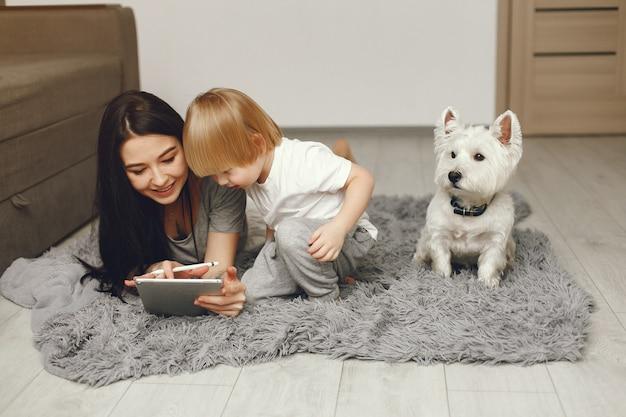 Madre e hijo pequeño divertido en casa con perro