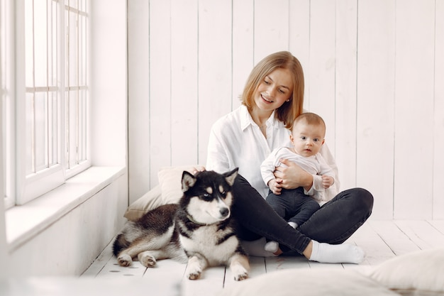 Madre e hijo pequeño jugando con perro en casa