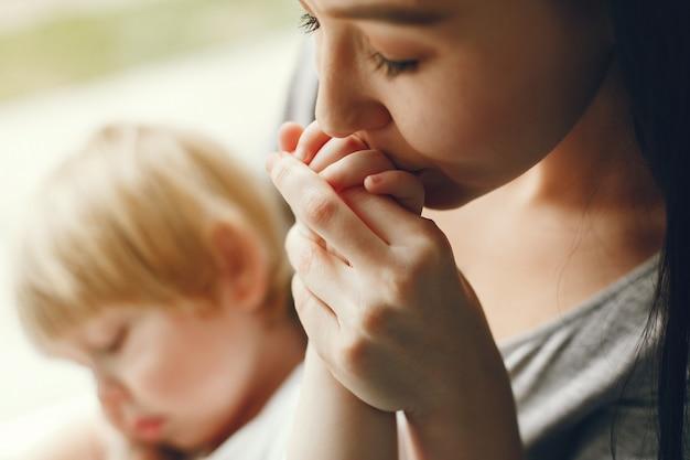 Madre e hijo pequeño sentado en el alféizar de una ventana