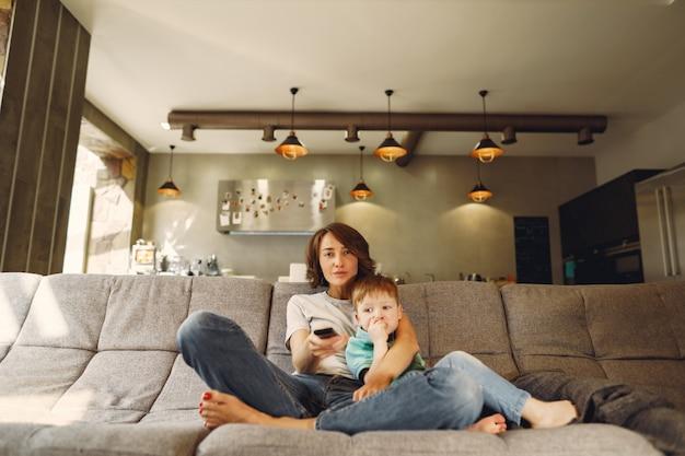 Madre e hijo pequeño sentado y viendo televisión