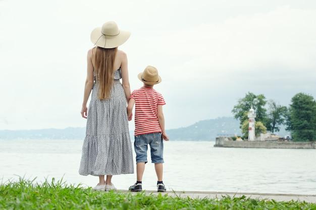 Madre e hijo de pie en el muelle. mar sobre un fondo, faro y montañas en la distancia. vista trasera