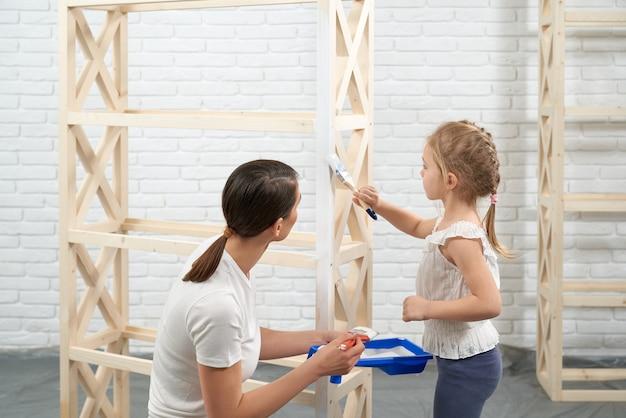 Madre e hijo pintando estante de madera en casa