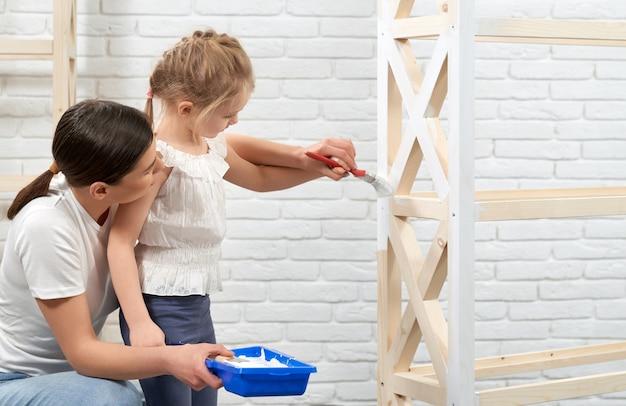 Madre e hijo pintando estante de madera.
