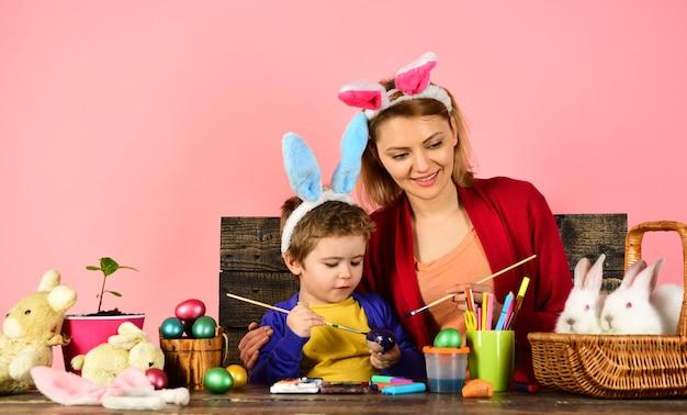 Madre e hijo pintando huevos de pascua huevo de pascua decorando familia feliz