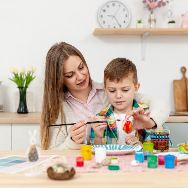 Madre e hijo pintando juntos los huevos de pascua