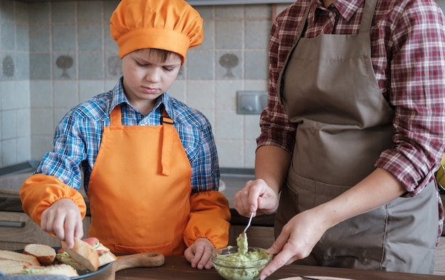 Madre e hijo preparan deliciosos bocadillos con aguacate, salmón, queso y tomates en la cocina. preparando un desayuno familiar