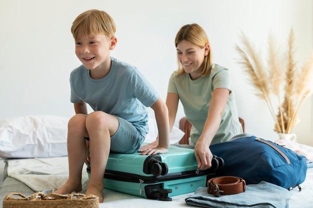 Madre e hijo preparando una maleta para sus vacaciones