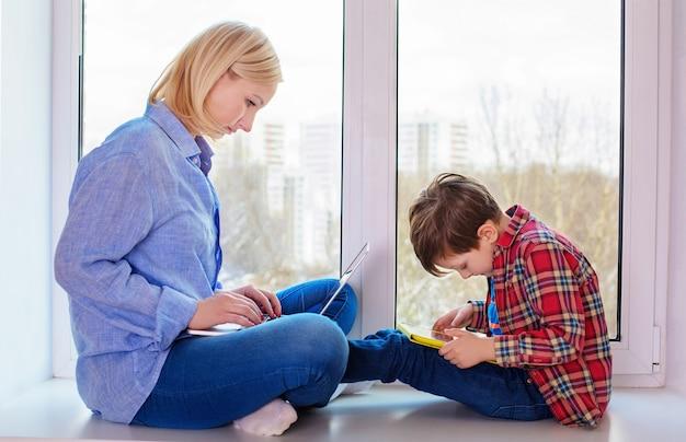 Madre e hijo sentados en un alféizar de la ventana con gadgets