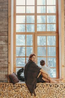 Madre e hijo sentados en el alféizar de la ventana y jugando.