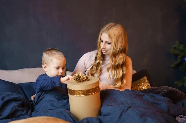 Madre e hijo sentados en la cama abriendo regalos