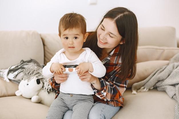 Madre e hijo sentados juntos y jugando con joystick