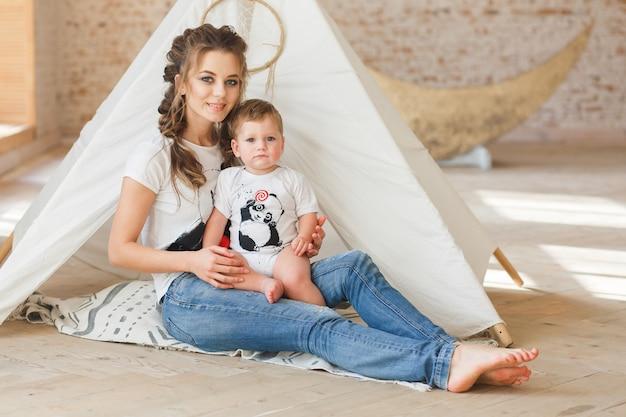 Madre e hijo sentados posando cerca de la tienda de campaña en loft estudio con fondo de pared de ladrillo