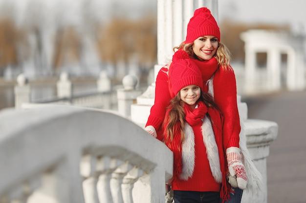 Madre e hijo con sombreros de invierno tejidos en vacaciones familiares de navidad. gorro y bufanda de lana hechos a mano para mamá y niño. tejer para niños. prendas de abrigo de punto. mujer y niña en un parque.