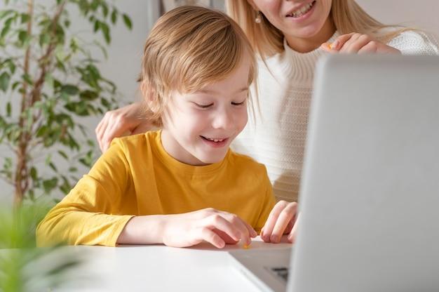 Madre e hijo sonrientes usando laptop en casa
