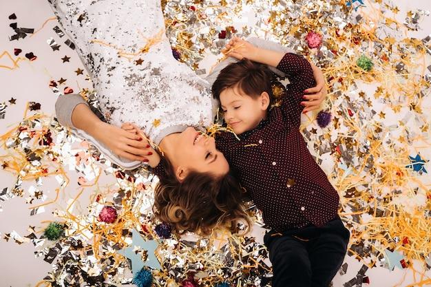 Madre e hijo yacen en el suelo en confeti sobre un fondo blanco.