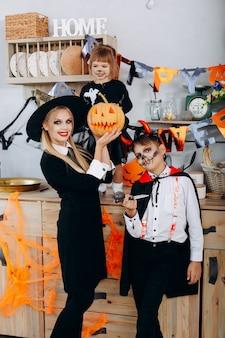 Madre e hijos en la cocina de pie en disfraces y mirando a la cámara