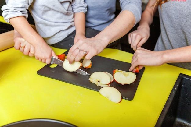 Madre e hijos cocinando en la cocina y divirtiéndose