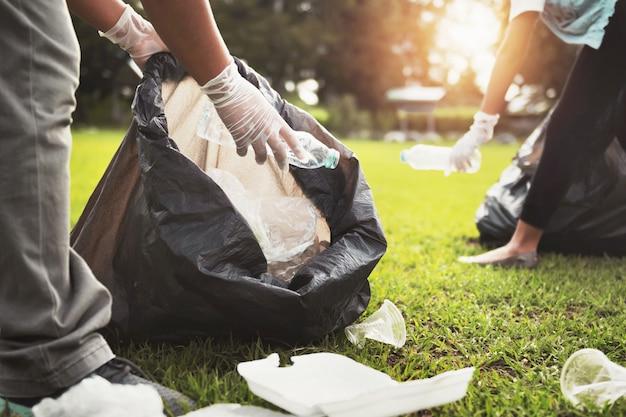 Madre e hijos manteniendo la botella de plástico de basura en una bolsa negra en el parque a la luz de la mañana