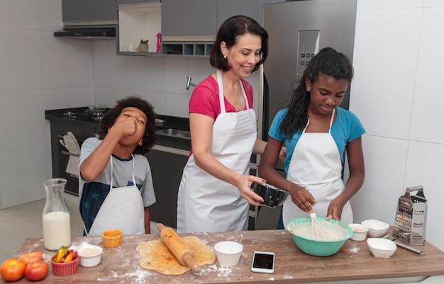 Madre e hijos preparando el almuerzo juntos en la cocina.